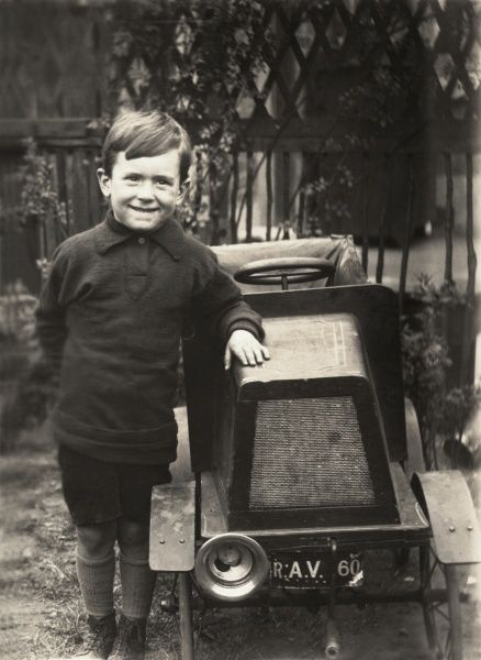 A little boy of about five or six years old looks as pleased as punch as he poses next to his very smart, luxurious and large toy pedal car