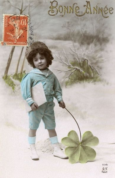 A boy stands in the snow holding a very large four- leaved clover Date: 1910