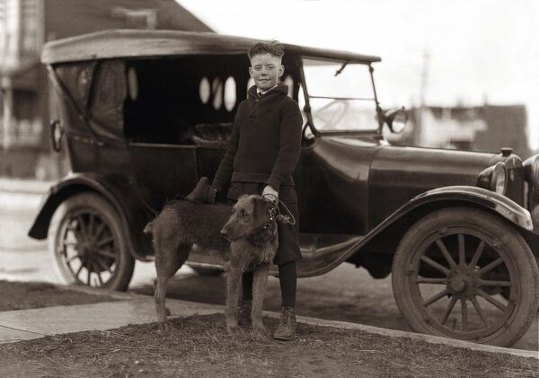 A boy of about ten or eleven poses in front of a car with his pet dog, a clipped Airedale terrier