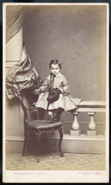 Small boy dressed in a frock (or possibly skirt & jacket) of horizontal stripes & with a pleated skirt, white collar & ribbon trim. He holds a round hat with pendant ribbons