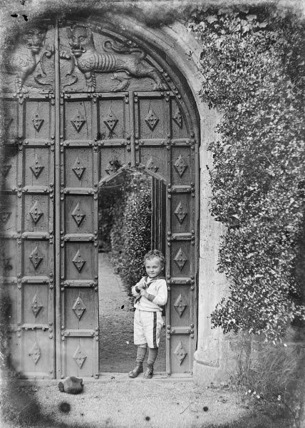 A small boy leans against a doorway cut into a far larger set of impressively carved wooden doors in a gateway. He is wearing a sailor suit. (Picture 1 of 3)