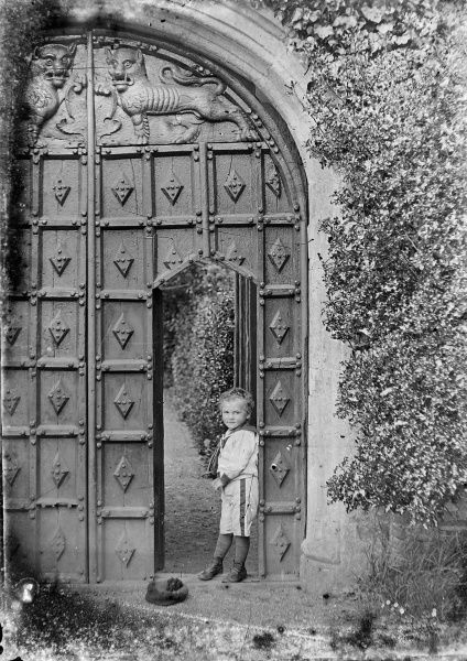 A small boy leans against a doorway cut into a far larger set of impressively carved wooden gates. He is wearing a sailor suit but has discarded his cap (Picture 2 of 3)