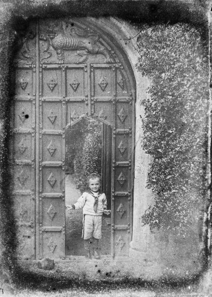 A small boy stands in a doorway cut within two large intricately carved wooden gates. He is wearing a sailor suit (Picture 3 of 3)