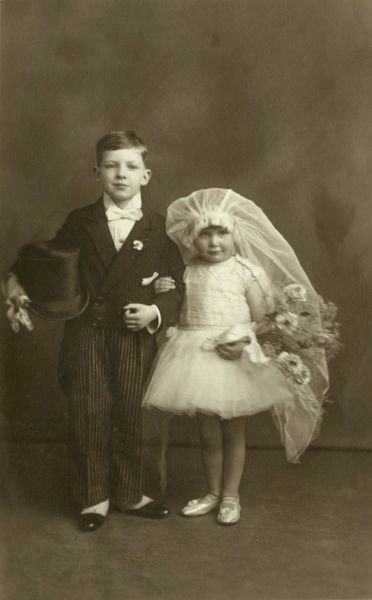 A small boy and an even smaller girl, dressed up as bride and groom. Date: circa 1920?