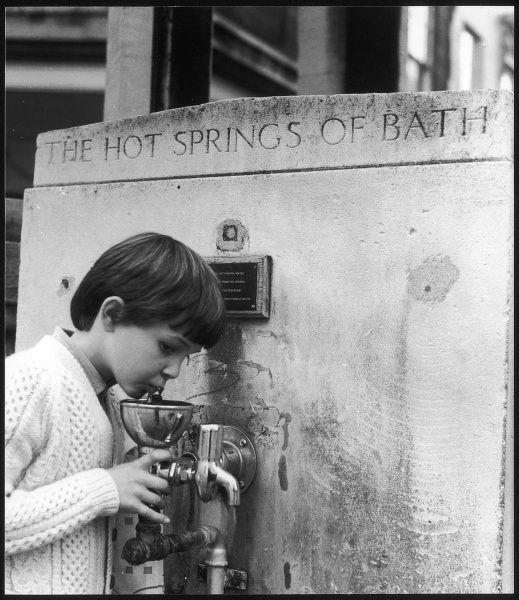 Boy drinks from a water fountain containing hot spring water, Bath
