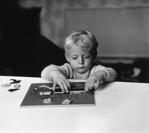 A small boy playing with a puzzle. Date: circa 1960