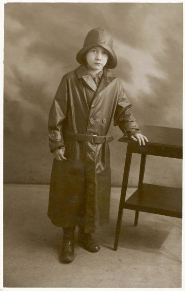 A small boy is well protected against inclement weather in a long double-breasted waterproof coat, a hat with upturned brim & a pair of Wellington boots