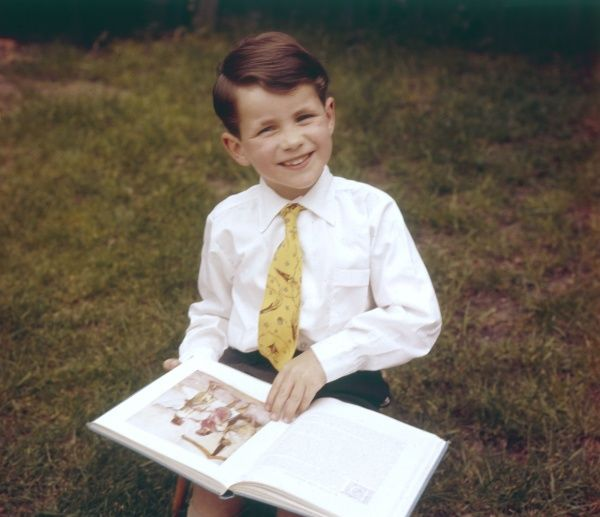 A boy reading an illustrated book outside. Date: 1950S