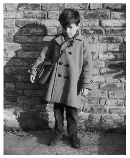 A cheeky-looking boy wearing a duffle-style coat with a satchel over his shoulder