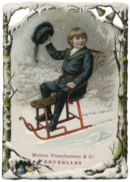 A boy on a sledge in the snow waves his hat