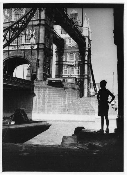 A boy stands in the shadow of Tower Bridge, London, to admire it