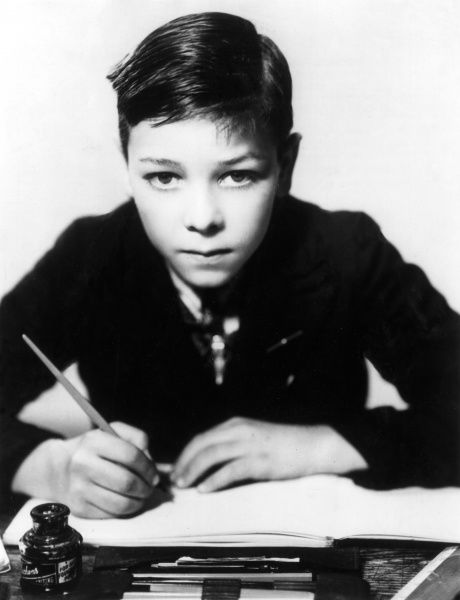 A rather wide-eyed little boy, writing at a desk, a bottle of ink and a selection of pens to hand. Date: 1930s