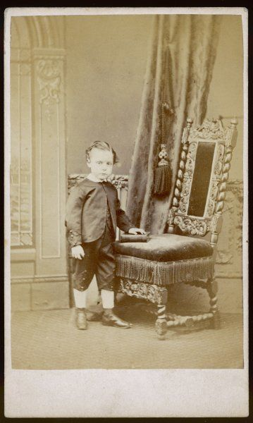A small boy poses next to a large chair. He wears a Zouave jacket with diamond shaped ornament on the cuffs, knickerbockers, boots & white socks