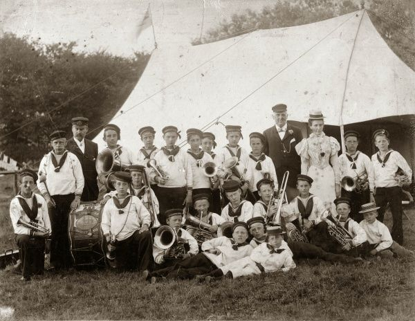 The Boys Band of the Training Ship Indefatigable pose for their photograph in a field, near a tent -- probably at a local fete where they were performing