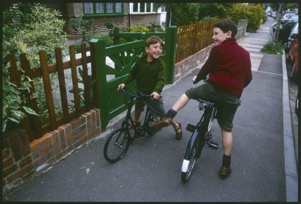 Two boys, brothers, enjoy fooling around on their bicycles outside their house during World War Two