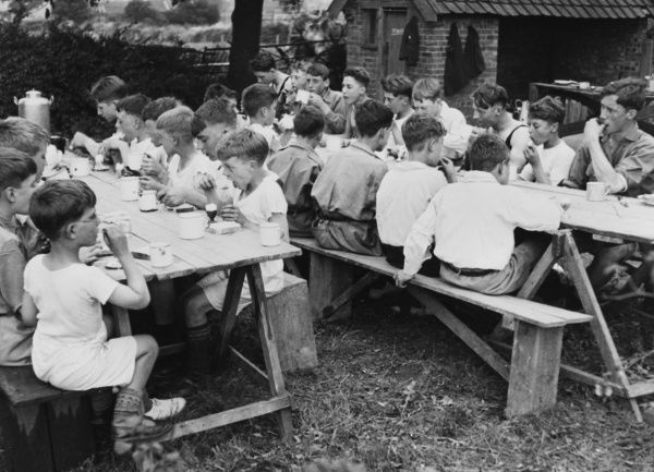 A group of boys from a Boys Club take their breakfast alfresco. They sit on long benches and eat a boiled egg with bread and a cup of tea