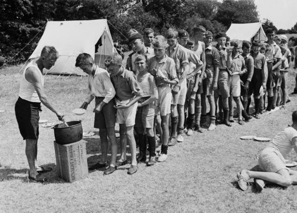 An orderly line of hungry boys from a Boys Club wait with bowl in hand for a helping of food served by the club leader. Two tents are seen in the background