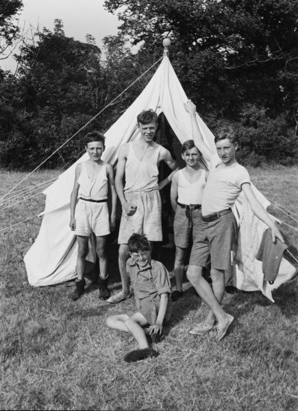 A group of five happy smiling boys pose proudly for a photograph outside of their tent