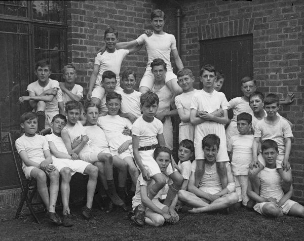 An informal gym class group photograph featuring 24 boys from a Boys Club of 1933, standing and sitting outside. Some of the boys sit on the shoulders of others