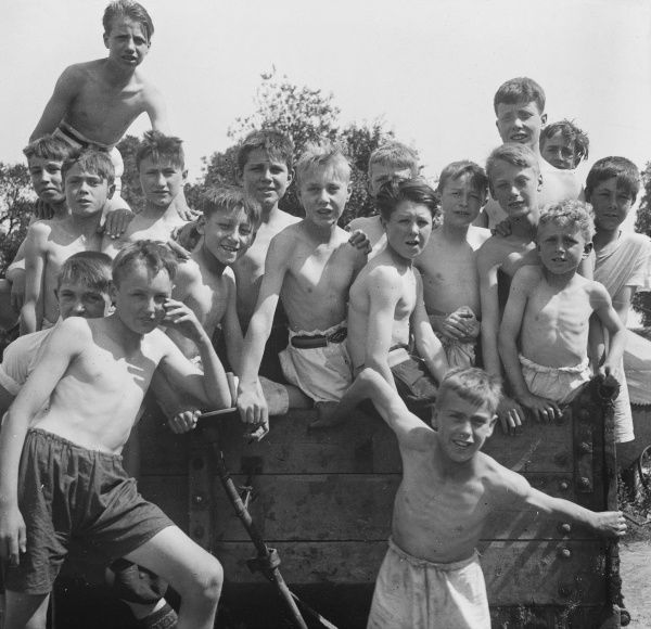 Eighteen shirtless boys pose happily in the sun for an informal group photograph on what looks like the back of a cart