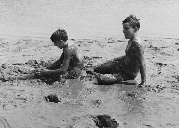 Two boys from a Boys Club, on the beach doing what boys do best; getting covered head to toe in mud
