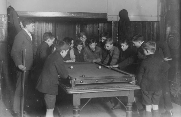 A group of fifteen boys cram around a snooker table during an evening game at a Boys Club