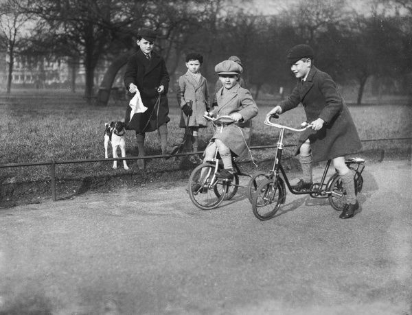 Well-dressed little boys in caps and overcoats in a London park, two riding their bicycles, watched by other boys with their dog on its lead