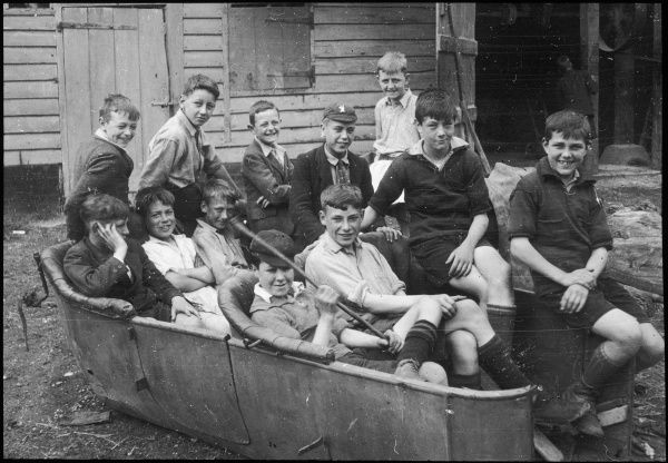 Twelve members of a boys club have a jolly time of it as they sit for a photograph in the remains of an old dilapidated car body
