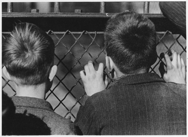 Two boys watch a band playing through the fence Date: 1930s