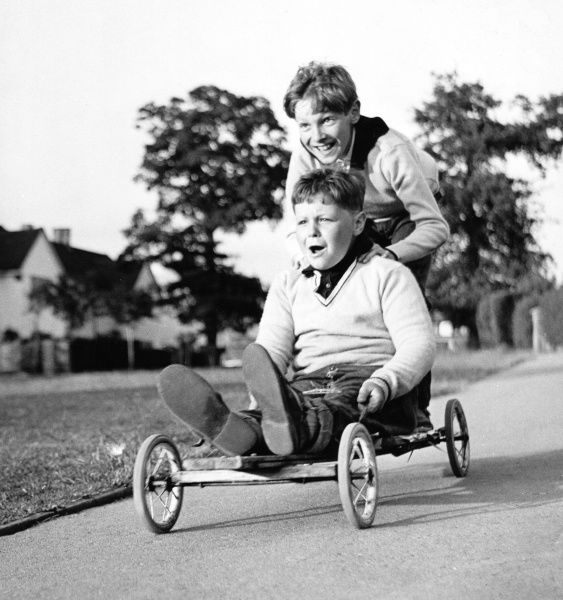 Two boys enjoying a ride on a home-made go-kart in Horley, Surrey
