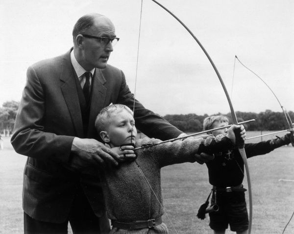 Boys learning archery at school are guided by their teacher. Date: 1950s