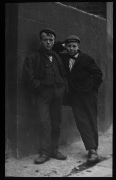 Two working class Edwardian boys leaning against a wall on a London street