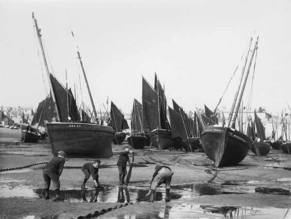 Four boys playing near a large pool in the sand in the harbour at St Ives, Cornwall. A large number of beached fishing boats can be seen in the background