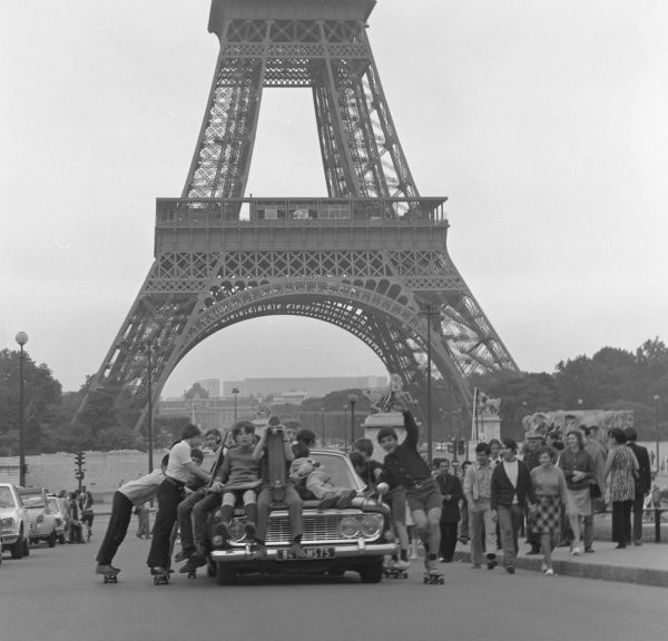 A gang of young teenage boys riding on top of a car, while others use it as a source propulsion as they stand on their skateboards, holding onto the side of the vehicle - close to the Eiffel Tower, Paris, France