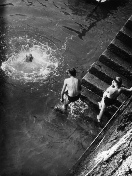 Boys enjoying themselves, swimming beside some steps, one of them wearing a snorkel and goggles. Date: 1950s