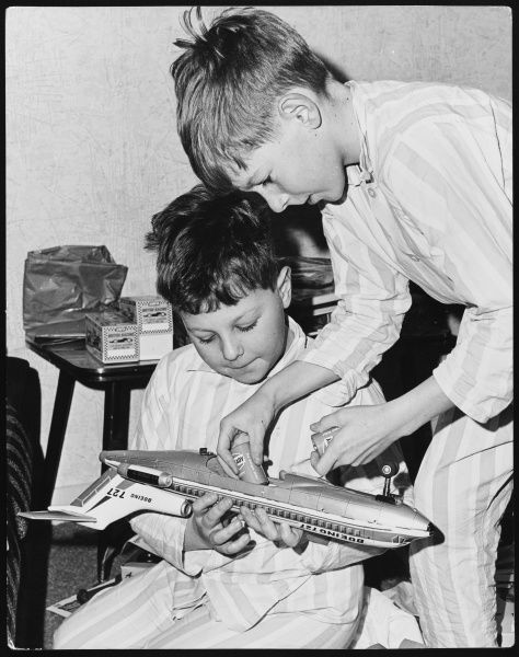 Two young boys, brothers, wearing stripy pyjamas, perhaps on Christmas morning, excitedly put batteries into their new model (Boeing 727) aeroplane