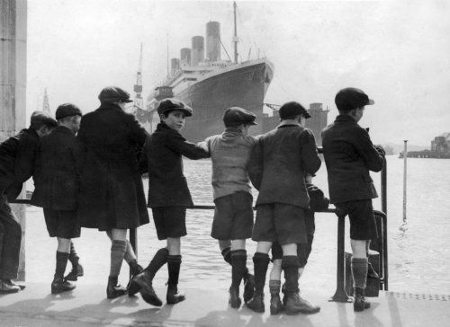 A group of boys lean against the dock railings and watch a steamship being built
