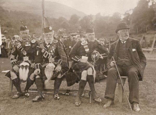 Scene at the annual Braemar Gathering, showing three men in traditional Highland costume and one man in a suit. Braemar in Scotland holds an annual Highland Games Gathering on the first Saturday in September, traditionally attended by the British Royal Family