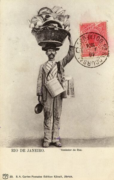 Superb postcard from Brazil depicting Street vendor (seemingly specialising in pots, cans and pans) in Rio de Janeiro. He carries the majority of his wares in a large tin tub balanced on his head! Date: 1904