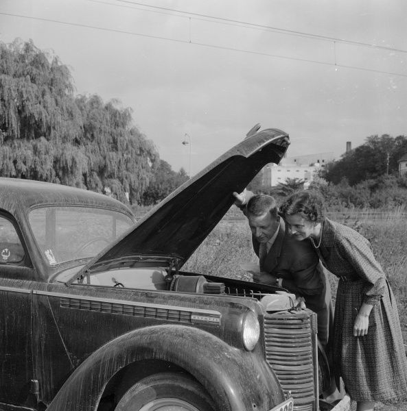 Checking the engine under the bonnet of an Opel Olympia, Landskrona, Sweden 1959. Date: 1959