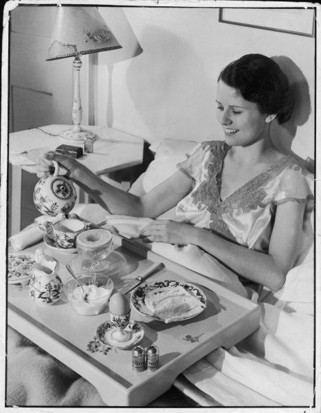 Smiling woman pours herself a refreshing cup of tea before tucking into a feast of grapefruit, boiled egg from an egg cup & toast served on a tray
