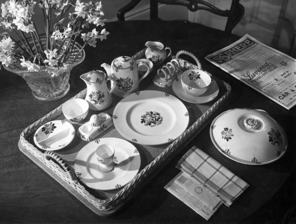 A wonderful breakfast set in dainty china, served on a wicker tray. A napkin, the morning post and a copy of The Sphere. What more could one ask for? Tea and toast? Date: 1930s