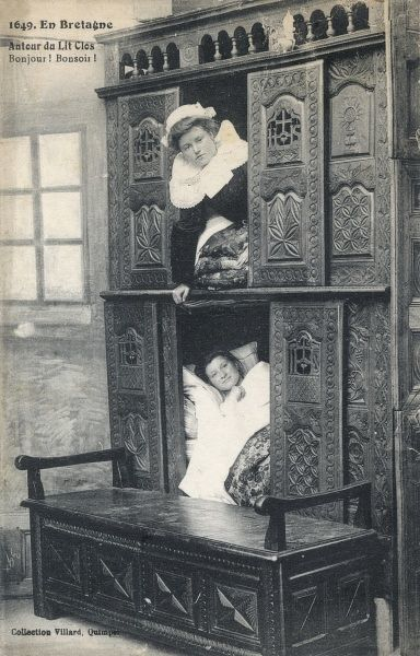 Two Breton ladies settle in for a good nights sleep in these enclosed beds(lits- clos)