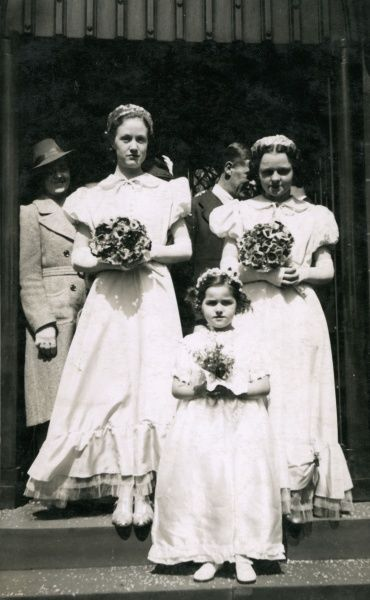 Three bridesmaids, with bouquets in their hands and confetti at their feet. Date: circa 1930s