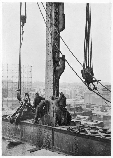 Construction on an unnamed bridge, probably in New York. Workmen placing into position one of the immense uprights 200 feet above the river