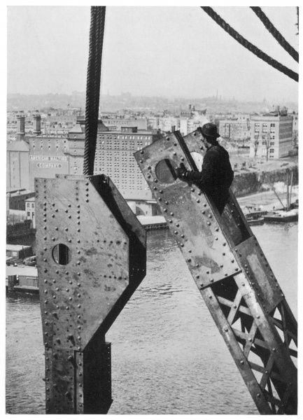 Construction on an unnamed bridge, probably in New York. Workmen putting a cross beam into place