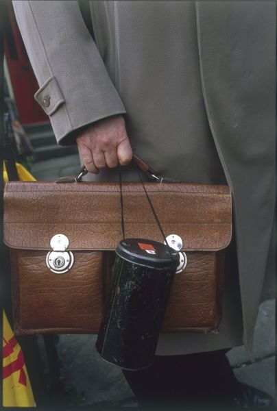 A businessman goes to work in London, carrying his briefcase and his gas mask case