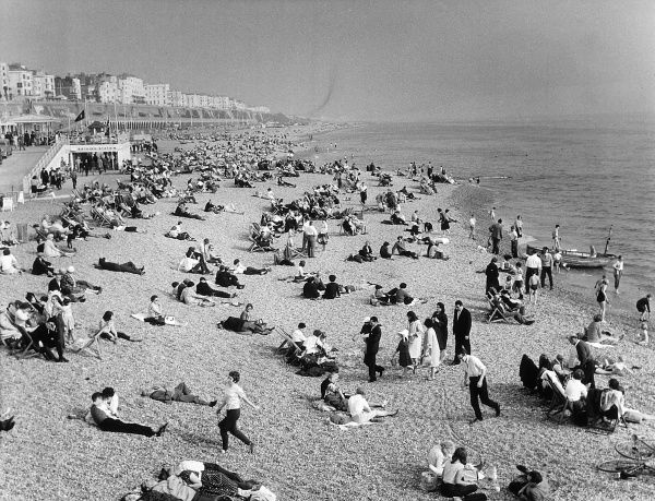Holidaymakers sprawl in the sun on Brighton's pebbly beach, Date: 1962