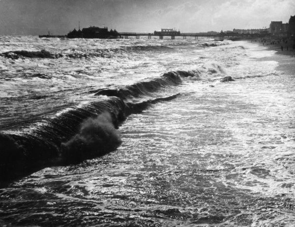 A lovely study of waves rolling onto the beach at Brighton, Sussex, England, with the West Pier in the background. Date: 1950s