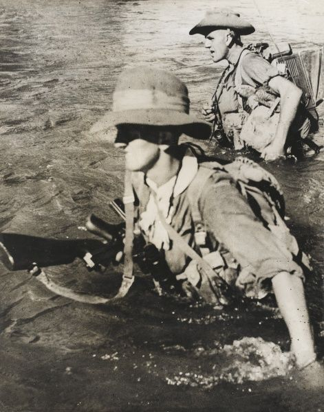 Two members of the British 36th Division (consisting of the Royal Scots Fusiliers, the Royal Welsh Fusiliers and the East Lancashire Regiment) in Burma wading through a river on the way from Hopin to Mohnyin